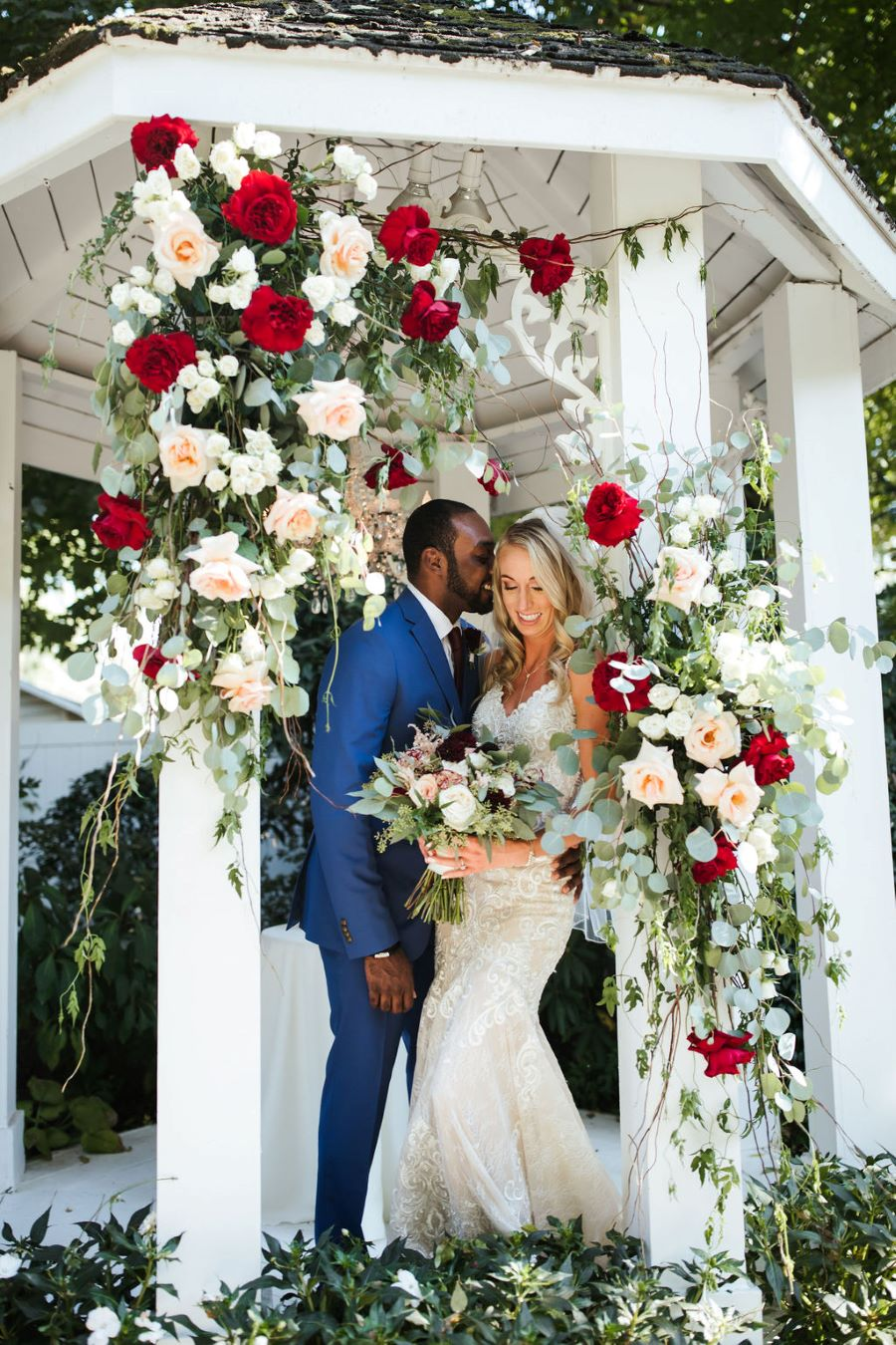 Bride and groom posing in pagoda with rose details / Classic / Fall / October / Maroon