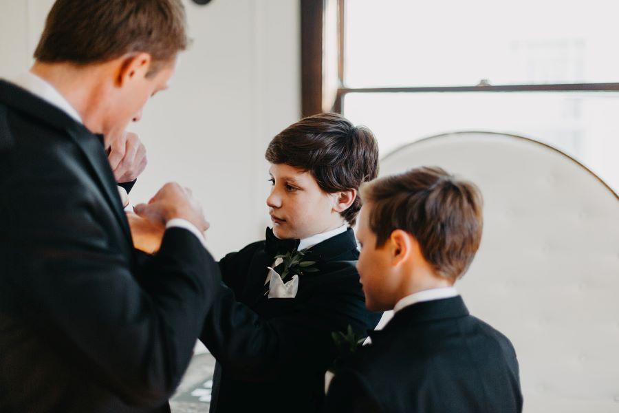 Groom's sons helping him adjust his tux before garden wedding / elegant / fall / november / pink / gold / green
