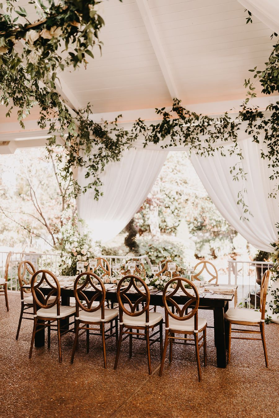 Table in garden reception space underneath draping greenery / elegant / fall / november / pink / gold / green