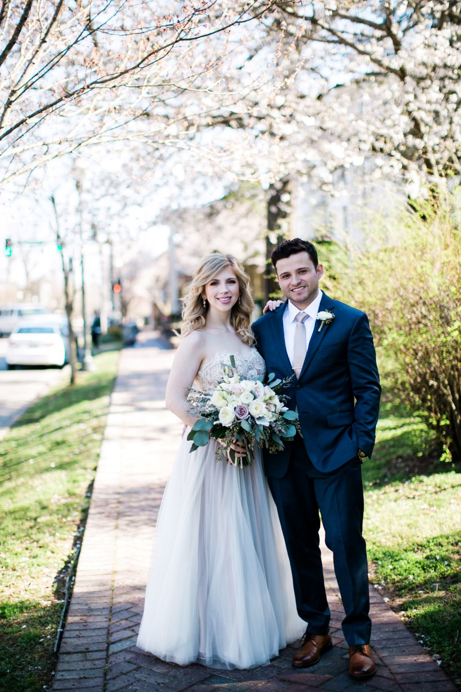 Bride and groom posing on brick sidewalk in front of wedding venue / Elopement / Spring / March / Dusty Rose