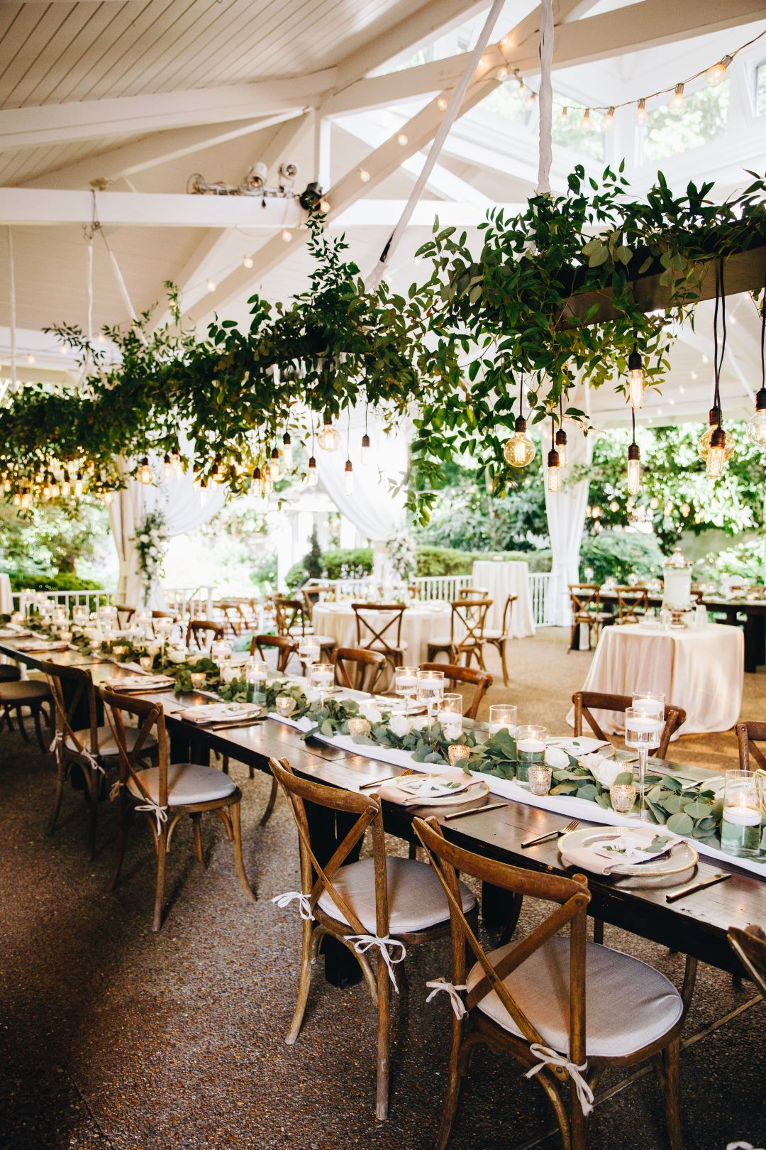 Long farmhouse table with greenery chandelier at earthy summer garden wedding in September, neutrals & greenery