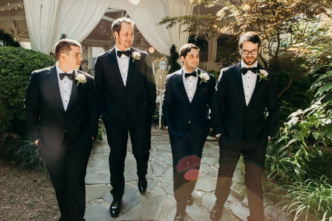 Groomsmen walking in the garden at earthy summer garden wedding in September, neutrals & greenery