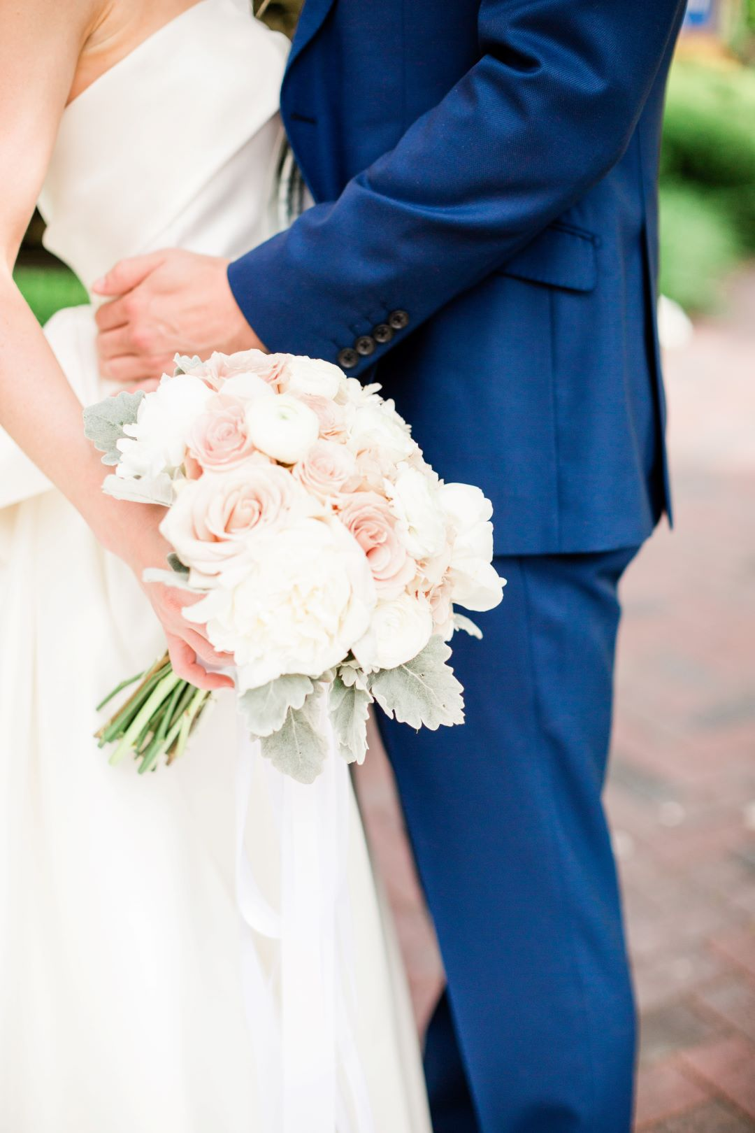 CJ's Off The Square   Close up of groom holding bride's waist and highlighting bouquet of blush roses